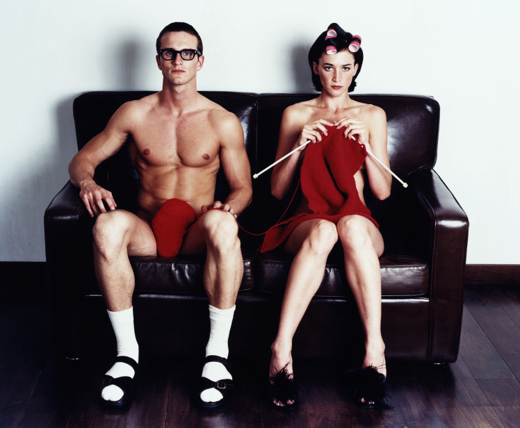 Naked couple sitting on couch, woman knitting, portraitCreativ